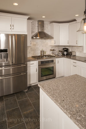 White kitchen design with gray accents and stainless steel appliances.