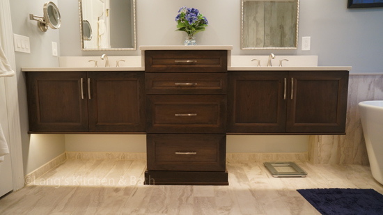 Floating vanity with a central floor mounted cabinet.