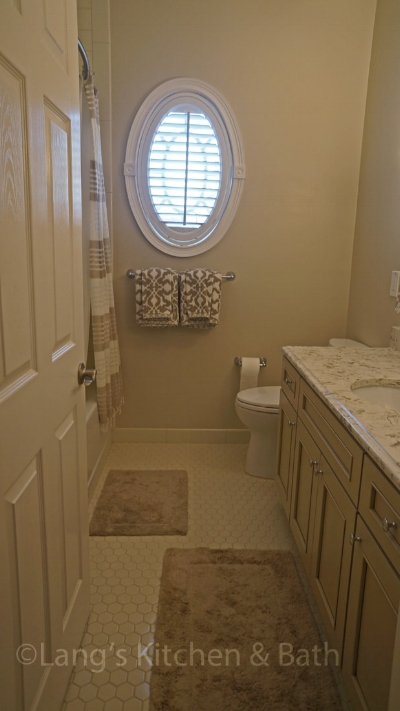 Hall bathroom design with shower, toilet, and vanity