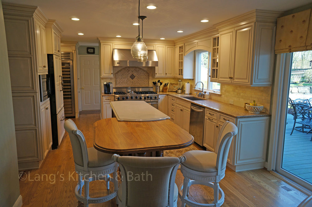 Traditional kitchen design with quartz and wood countertop on island.