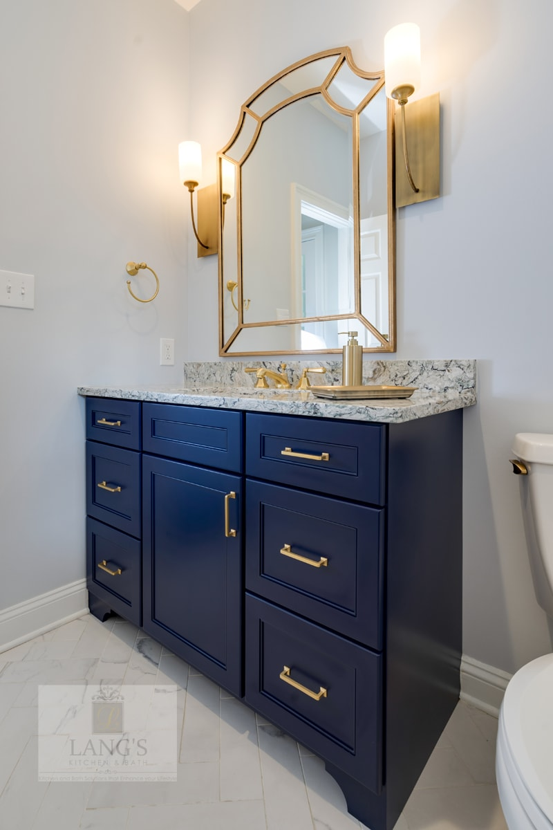 Powder room design with blue vanity and brass fixtures