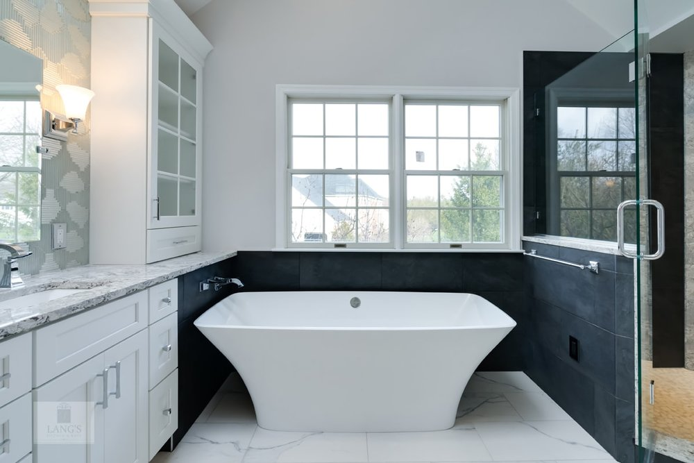 White freestanding bathtub with a black wall