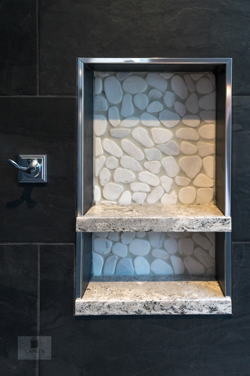 Black and white bathroom design with river rock shower niche