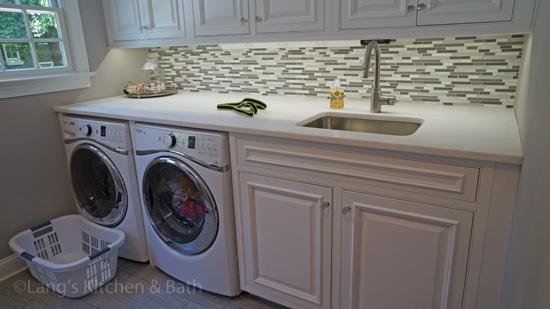 laundry room with mosaic tile backsplash