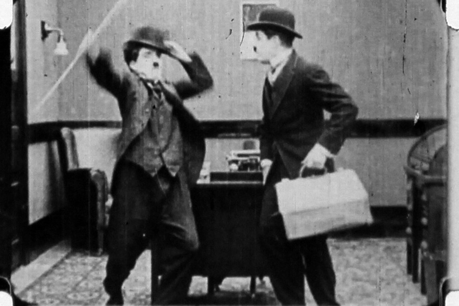 The frames show Chaplin (left) arguing with a look-alike in an office.
