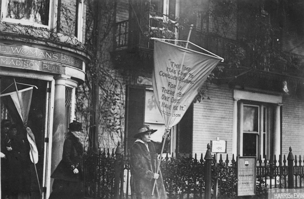 "The day after the police announce that future pickets would be given limit of 6 mos. in prison, Alice Paul led picket line with banner reading ""The time has come to conquer or submit for there is but one choice - we have made it."" She is followed by Mrs. Lawrence Lewis [Dora Lewis]. This group received 6 mos. in prison."