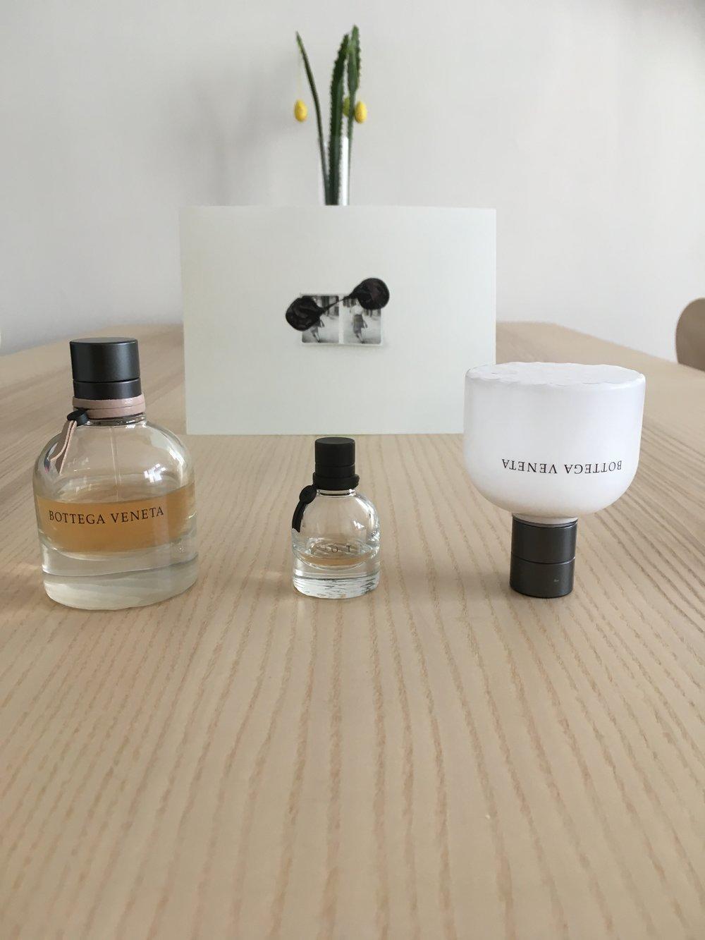 parfumovaná voda, miniatúra na cesty a telové mlieko, ktoré, ak nanesiem pred aplikovaním parfumu, vôňu ešte znásobí..v pozadí pohľadnica z výstavy  Lucie Tallovej  s názvom Druhý archív