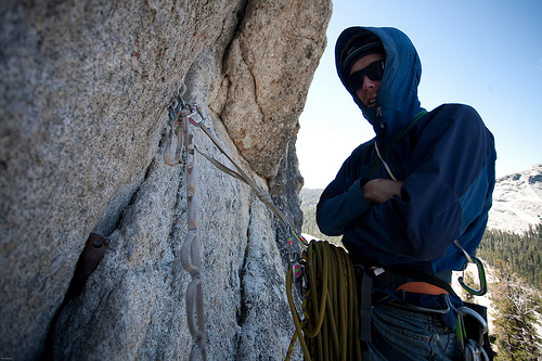 Sam at a cold, windy, shaded belay on West Crack, Daff Dome, Tuolumne, CA.
