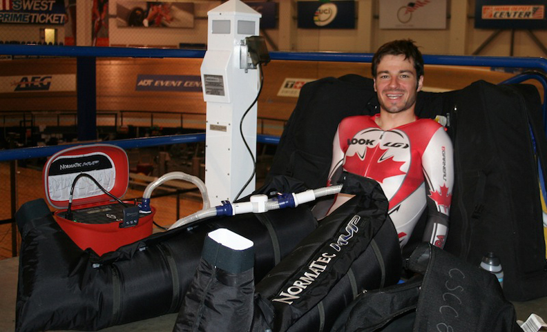 Zach Bell spends some time in his Normatec boots in between track sessions.