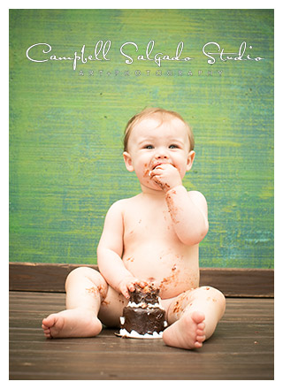Campbell Salgado Studio portrait of a one year old eating cake.