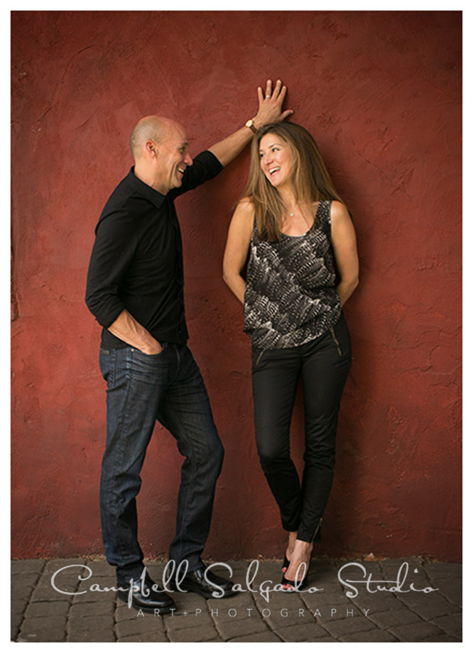 Portrait of couple against red wall by Campbell Salgado Studio.