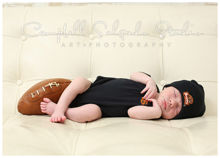 Portrait of baby boy in OSU gear on white couch by Campbell Salgado Studio.