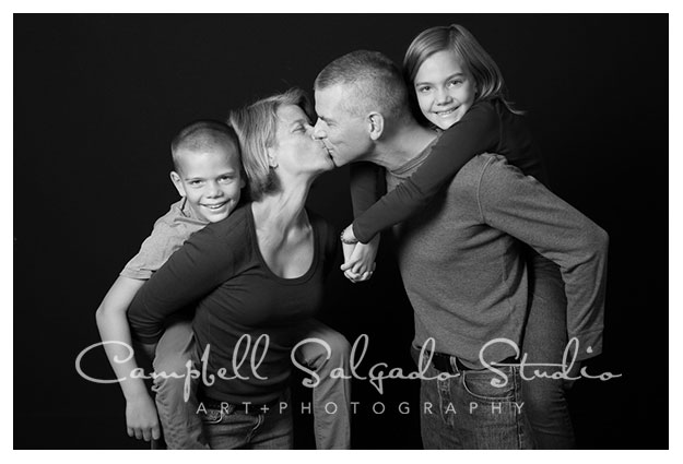 Family portrait in black and white by Campbell Salgado Studio in Portland, Oregon. Kisses and piggy back rides by parents.
