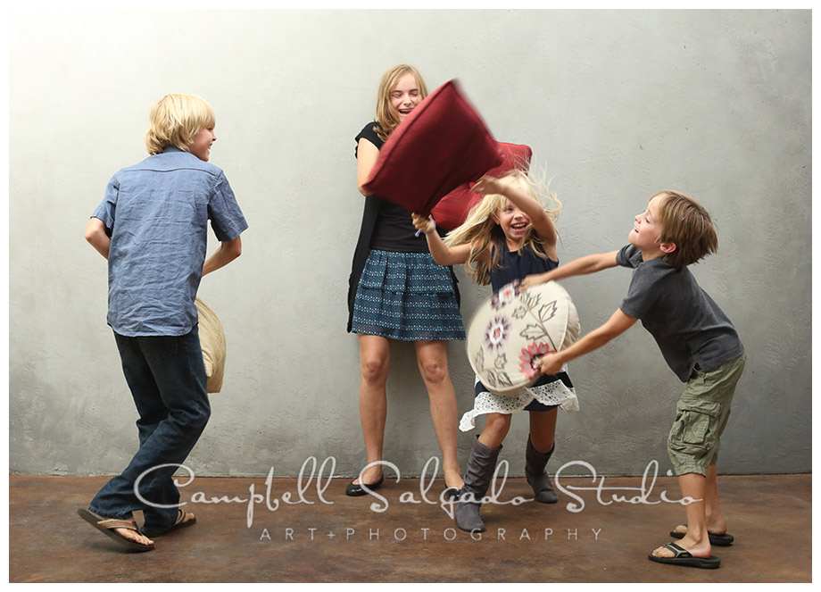 Portrait of kids having a pillow fight at Campbell Salgado Studio in Portland, Oregon.