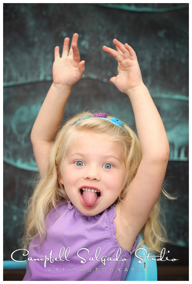Portrait of little girl being silly on copper background by Campbell Salgado Studio.