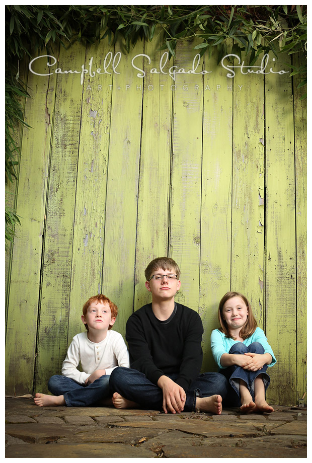 Portrait of siblings on green fence background at Campbell Salgado Studio.
