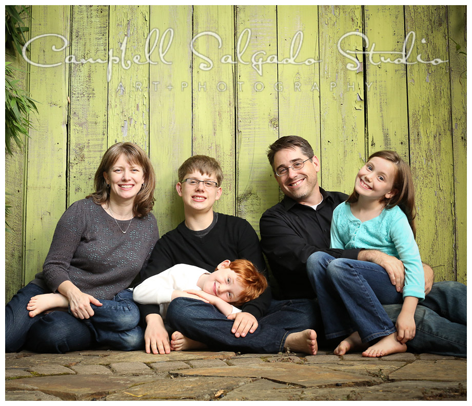 Portrait of family on green fence background at Campbell Salgado Studio.