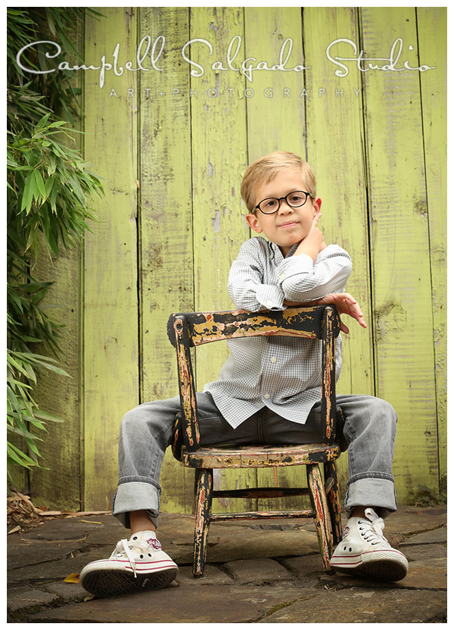 Portrait of young boy sitting on chair on green fence board background at Campbell Salgado Studio.