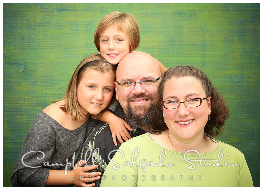 Portrait of family on green background at Campbell Salgado Studio.
