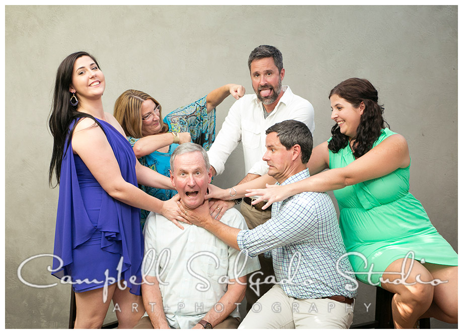 Portrait of family being silly on grey background at Campbell Salgado Studio in Portland, Oregon.