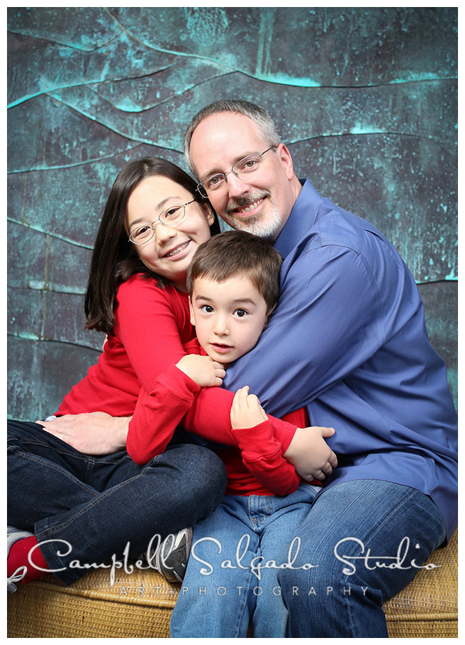 Portrait of family on copper blue background by Portland photographers Campbell and Salgado.