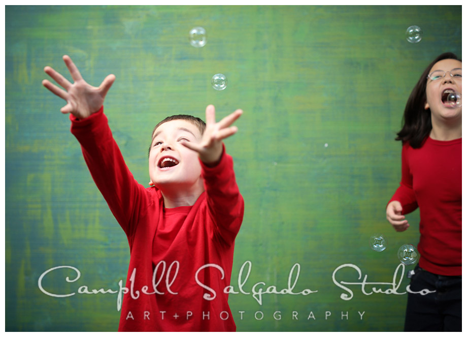 Portrait of kids playing with bubbles on green background at Campbell Salgado Studio.