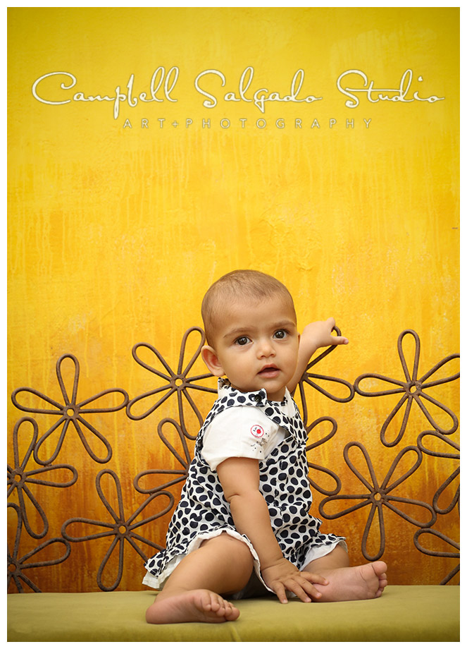 Portrait of baby girl on yellow background by Campbell Salgado Studio.