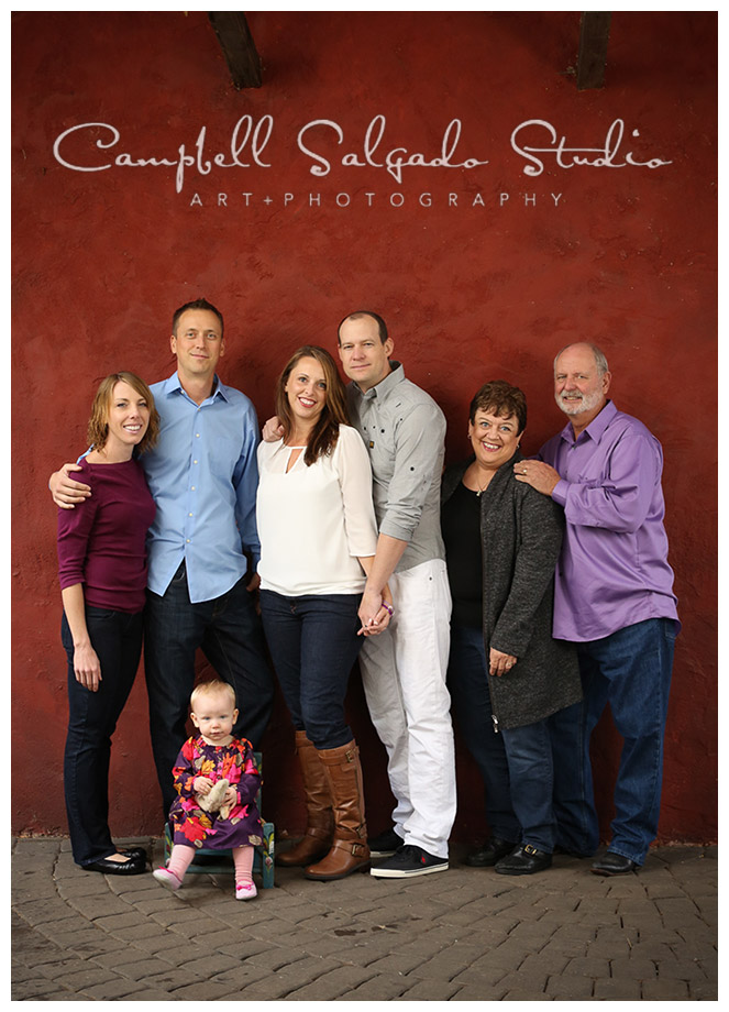 Portrait of extended family on red stucco background in Portland, Oregon at Campbell Salgado Studio.
