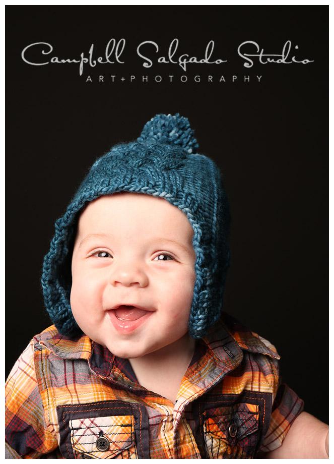 Portrait of baby boy in blue hat on black background at Campbell Salgado Studio.