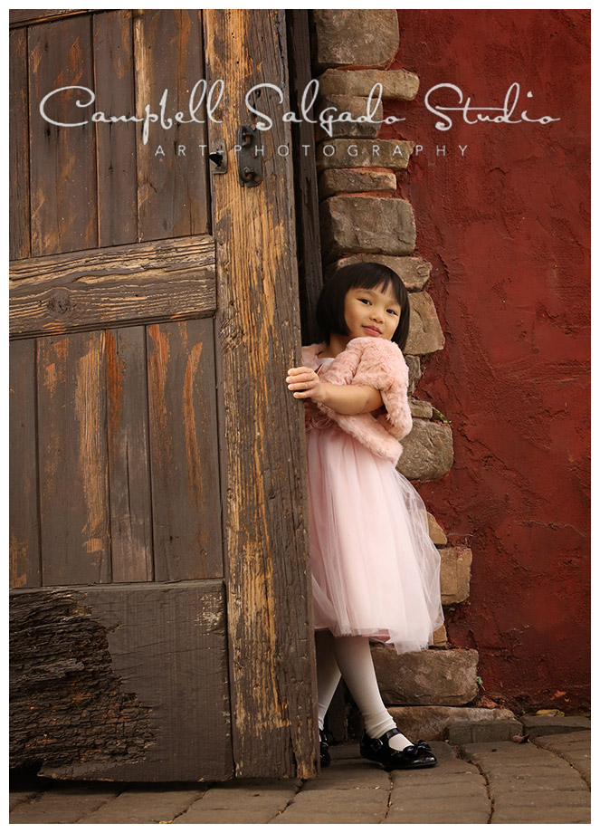 Portrait of young girl on rustic door background at Campbell Salgado studio.