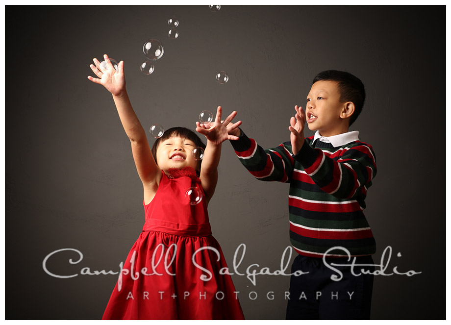 Portrait of siblings playing with bubbles on grey background in Portland, Oregon at Campbell Salgado Studio.