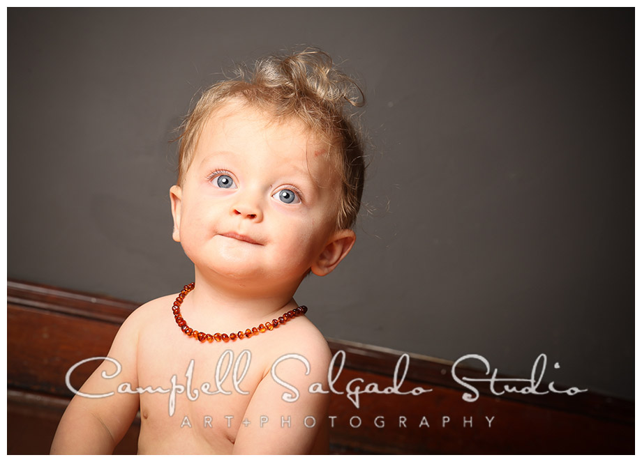 Portrait of baby wearing amber necklace on grey background at Campbell Salgado Studio.