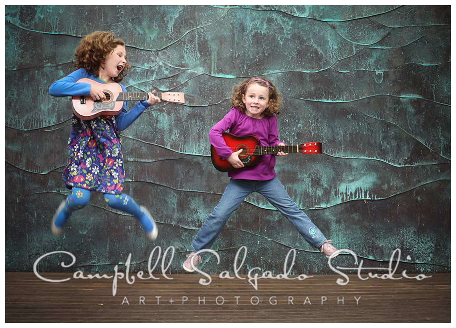 Portrait of sisters rocking out on copper background at Campbell Salgado Studio.