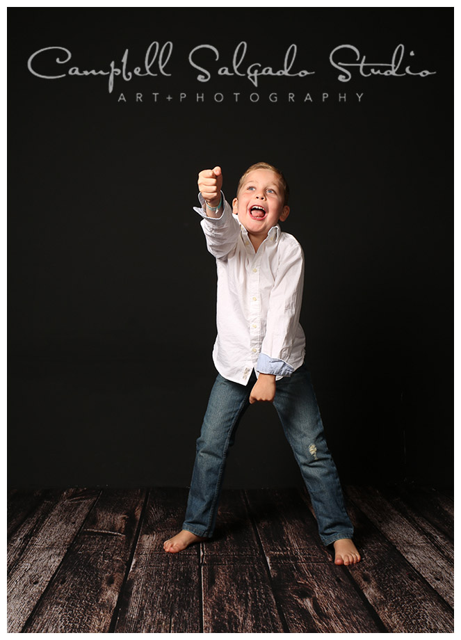 Portrait of young boy on black background at Campbell Salgado Studio in Portland, Oregon.