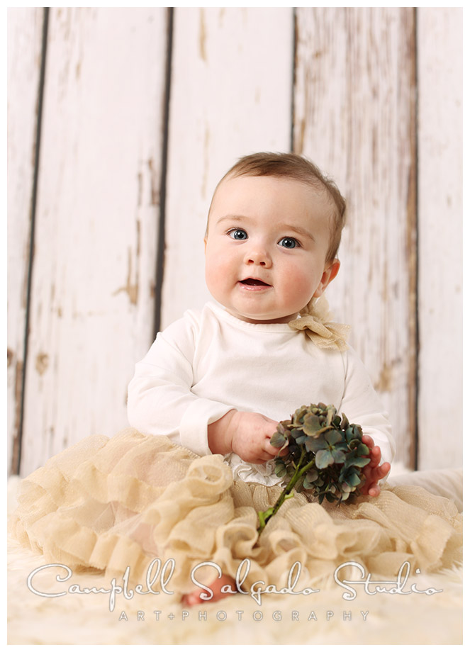 Portrait of baby girl on wood grain background with flower at Campbell Salgado Studio.