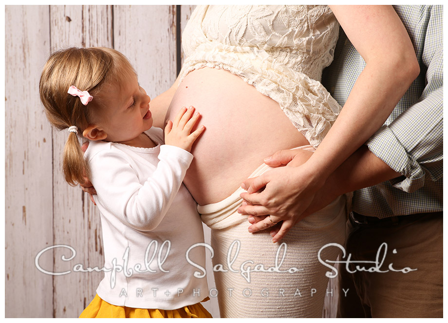 Portrait of pregnant mother and family at Campbell Salgado Studio in Portland, Oregon on wood grain background.
