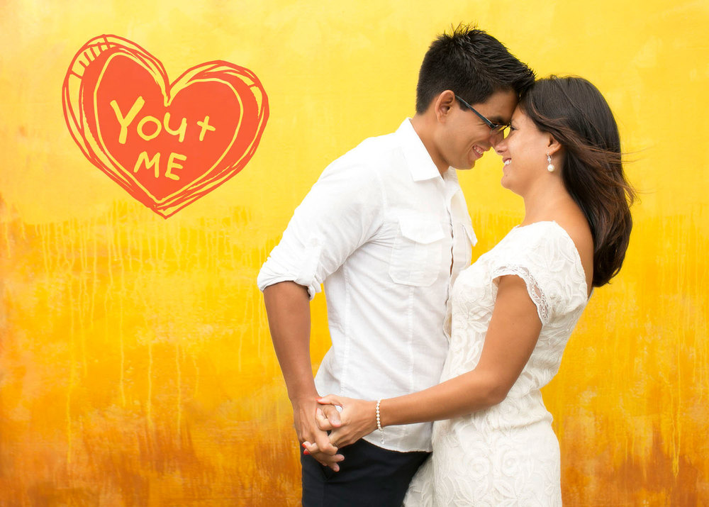 Campbell Salgado Studio portrait of a couple against a photo studio yellow background.