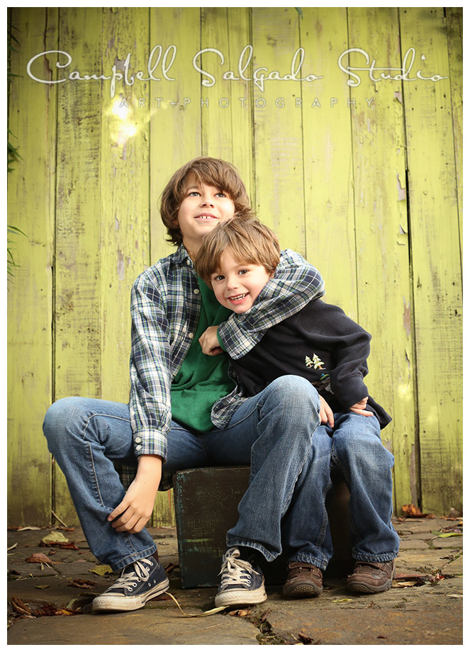 Portrait of brothers on green fence board background by Portland photographers Campbell and Salgado.