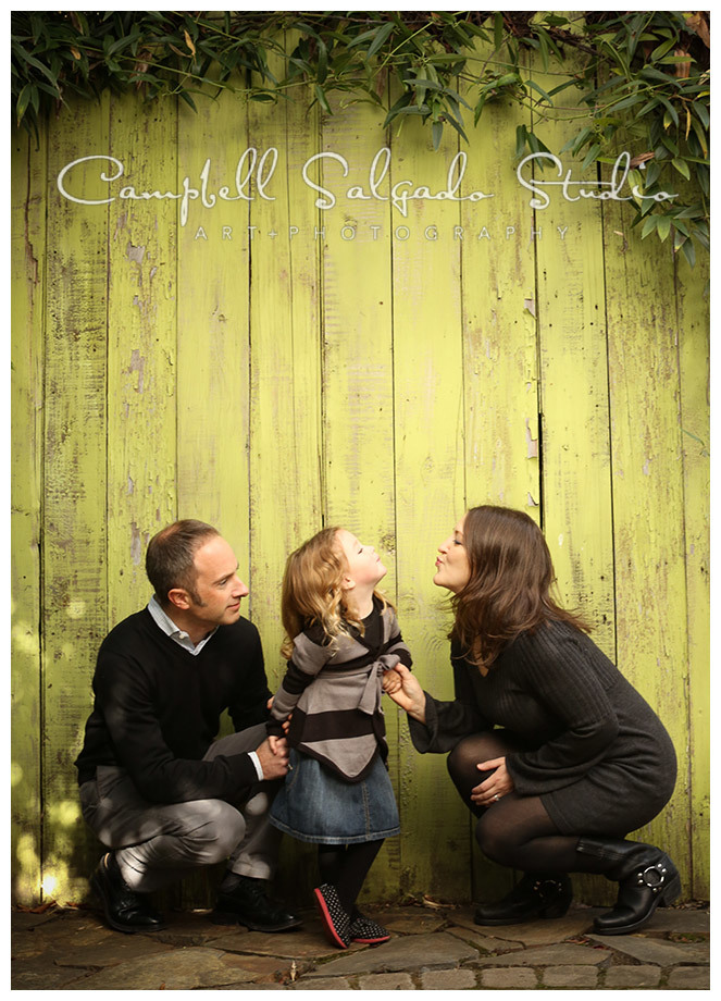 Portrait of family on green fence board background at Campbell Salgado Studio.