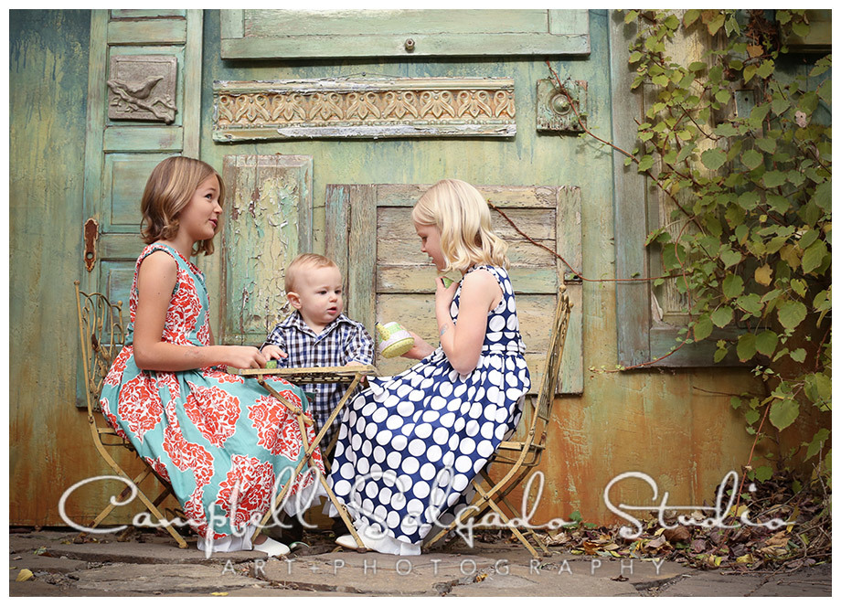 Portrait of kids having a tea party on vintage doors background at Campbell Salgado Studio.