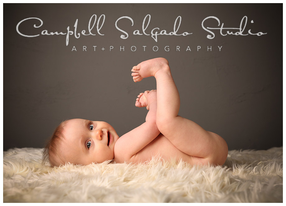 Portrait of baby against grey wall at Campbell Salgado Studio in Portland, Oregon.