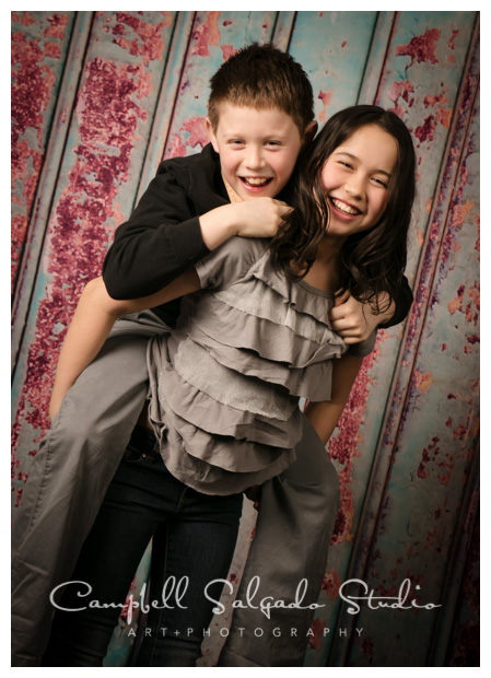 Child photographers at Campbell Salgado Studio in Portland, OR take portrait of a sister carrying her brother in a piggy back hold in color.