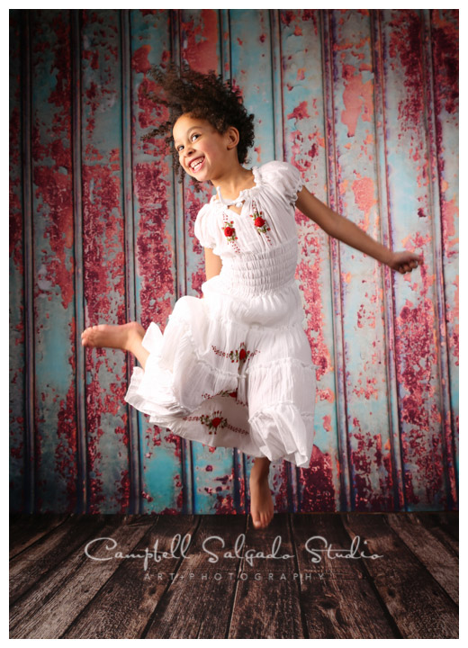 Girl jumping against a colored background by child photographers at Campbell Salgado Studio, Portland, Oregon.