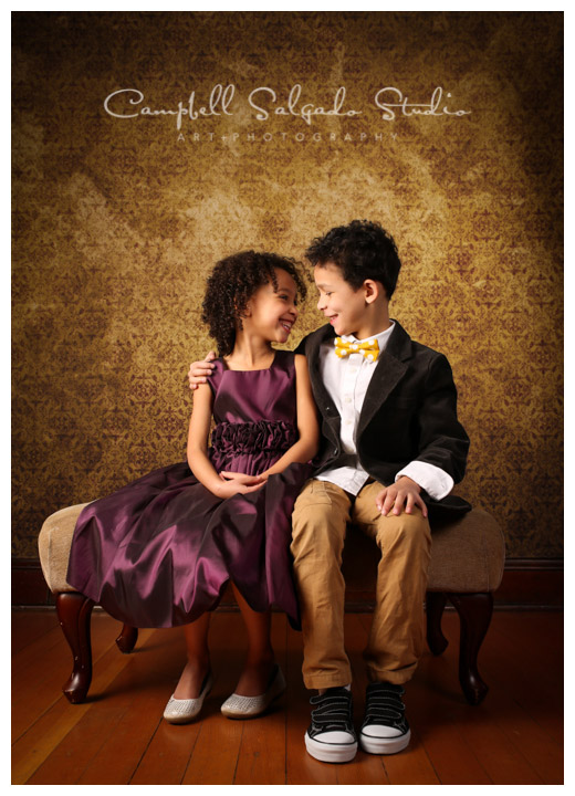 Brother and sister portrait against a gold background by child photographers at Campbell Salgado Studio, Portland, Oregon.