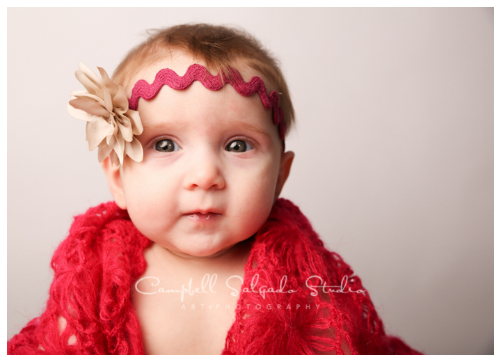 Portrait of baby girl in shawl and headband on white background at Campbell Salgado Studio.