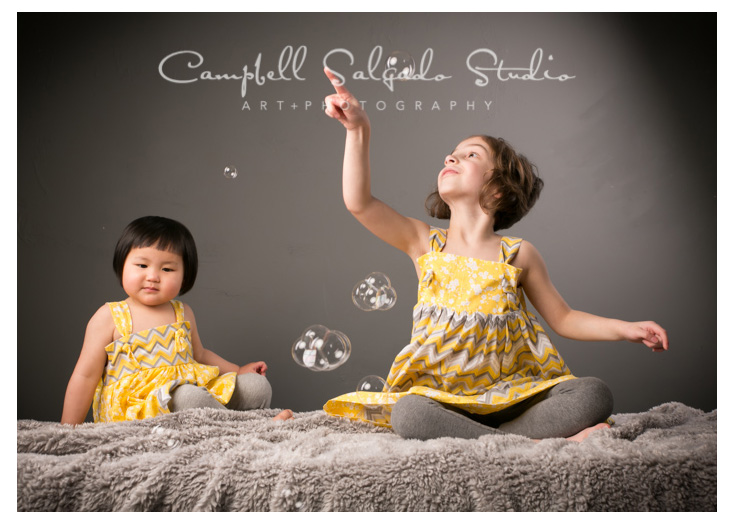 Portrait of sisters on grey wall at Campbell Salgado Studio in Portland, Oregon.