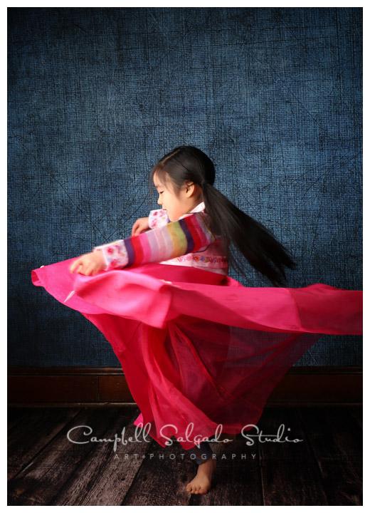 Portrait of little girl dancing on denim background at Campbell Salgado Studio.