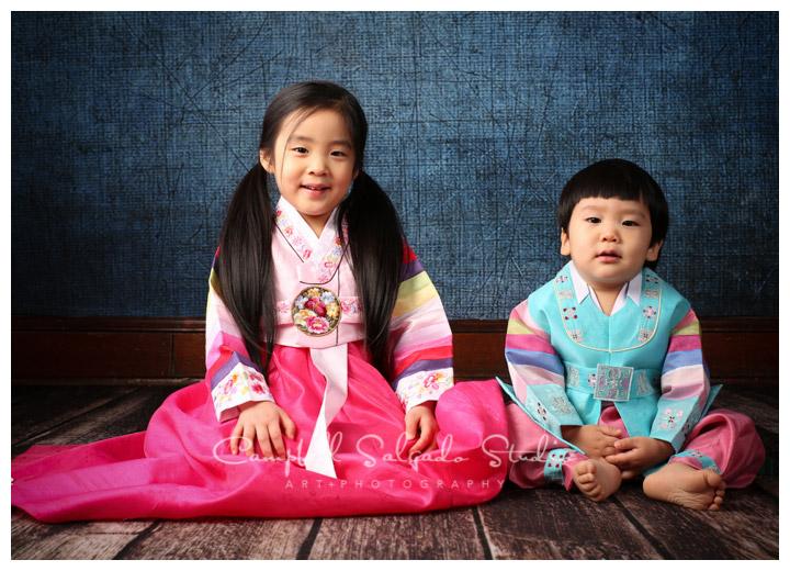 Portrait of siblings in traditional Korean dress on denim background at Campbell Salgado Studio.