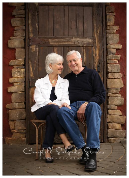 Portrait of couple on rustic door background at Campbell Salgado Studio.