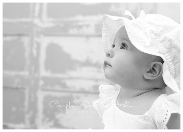 Portrait of baby girl on vintage doors background in Portland, Oregon at Campbell Salgado Studio.
